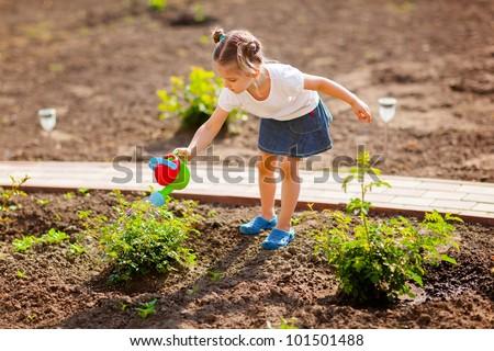 Little gardener watering flowers - stock photo