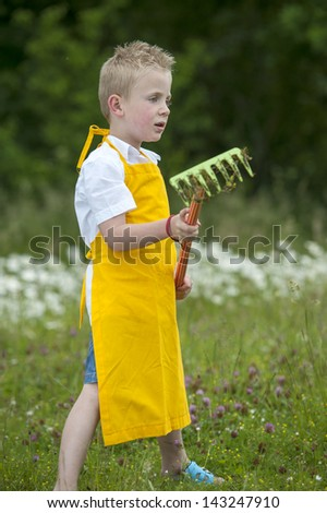 little gardening boy with rake an yellow apron - stock photo