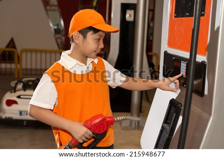 Little gas station attendant pushing buttons on the gas pump