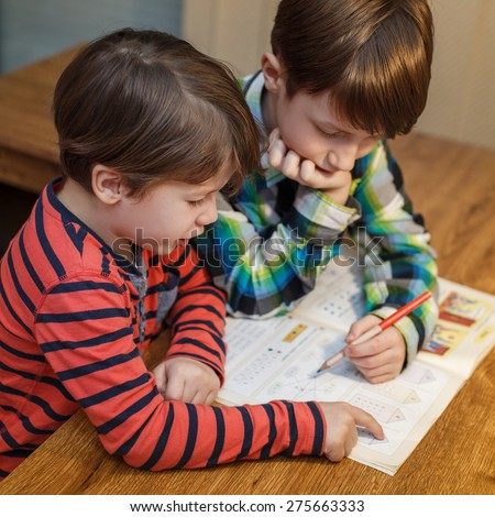 Little genius boy help his brother with homework, problem solving, education
