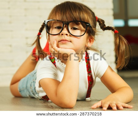 Little genius in glasses lying on the floor - stock photo