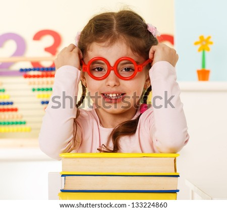 little genius in glasses with books - stock photo