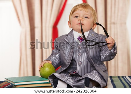 Little genius with apple and  books for reading - stock photo