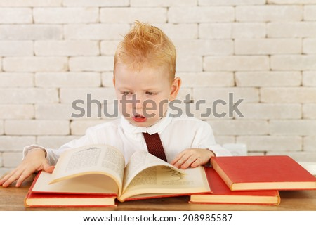 Little genius with books on Brick Wall background