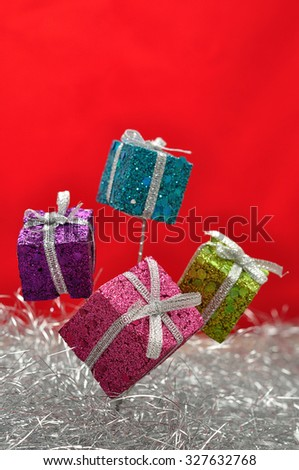 Little gifts in shinny wrapping for decorating a Christmas tree with silver tinsel and a red background - stock photo