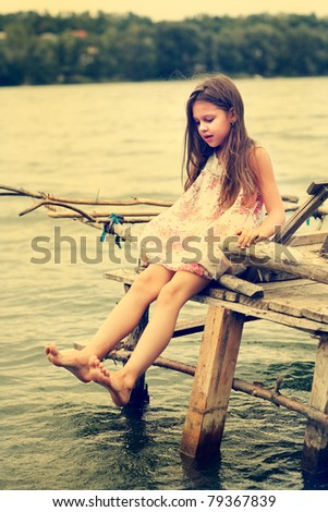 Little girl a park near the river - stock photo