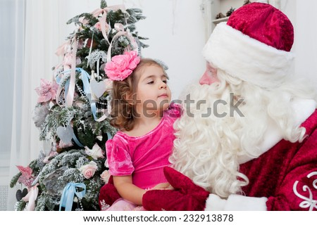 Little girl about something talks to Santa Claus