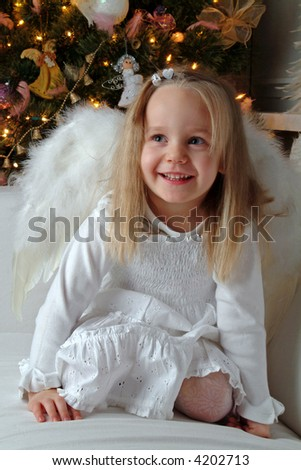 Little girl acting as an christmas angel. Christmas tree in a background.