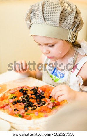 Little girl adding ingredients, vegetables and meat, in pizza - stock photo