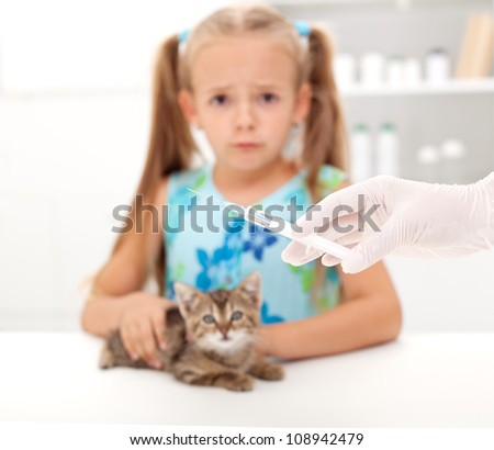 Little girl afraid for her kitten getting a vaccine at the veterinary - focus on syringe