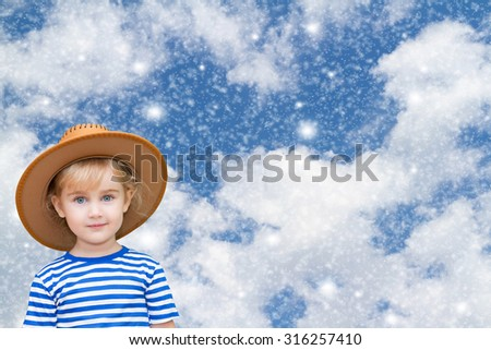 Little girl against the sky, snow and clouds.