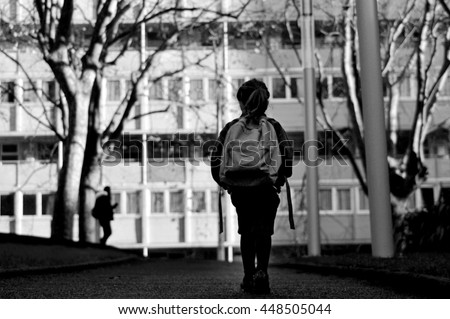 Little girl (age 6) with school bag walks to school alone by herself in the street. Education concept. vertical  copy space - stock photo