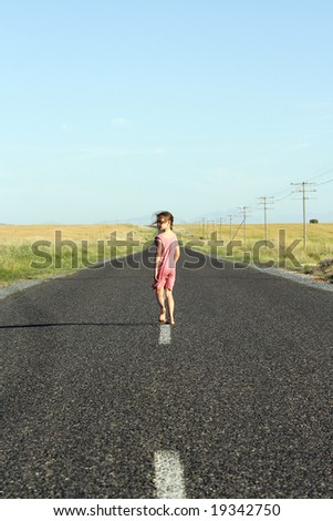 Little girl, aged seven, wearing a pink dress, walking down a tarred road and looking over her shoulder