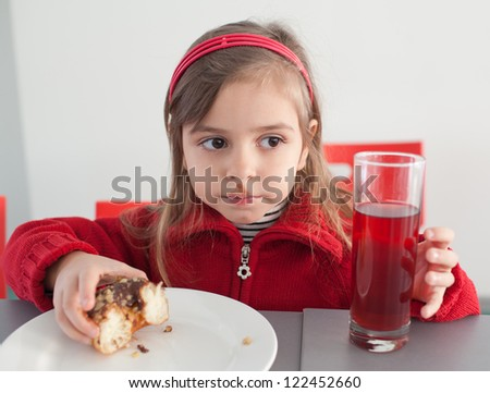 Little girl aged 5 to 6 years eating donut with chocolate and nuts. Indoors, portrait - stock photo