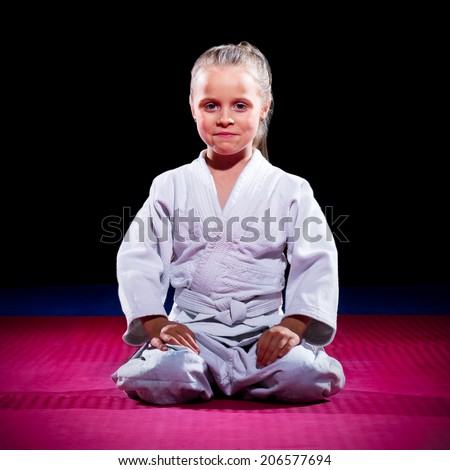 Little girl aikido fighter on black - stock photo