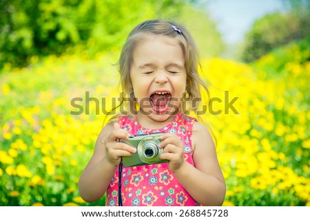 Little girl amazed by pictures on point and shoot camera - stock photo