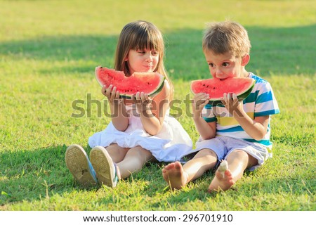 Little girl and a boy eating watermelon - stock photo