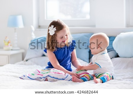 Little girl and baby boy, brother and sister playing in parents bed. Family with children in the morning. Kids play in white bedroom. Nursery crib bedding and textile for young child. Siblings love. - stock photo