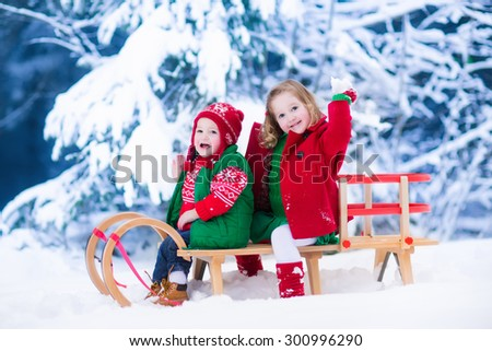 Little girl and baby boy enjoying a sleigh ride. Child sledding. Toddler kid riding a sledge. Children play outdoors in snow. Kids sled in snowy park. Outdoor winter fun for family Christmas vacation. - stock photo