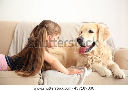 Little girl and big kind dog on sofa