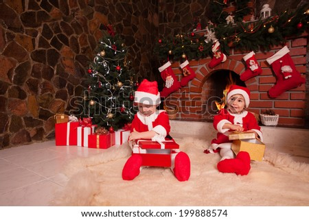 Little girl and boy are sitting near fireplace and christmas tree with gift boxes. Brother and sister in santa suits - stock photo