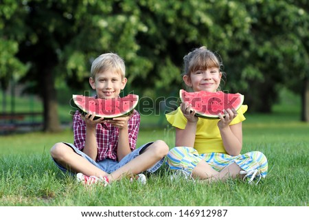 little girl and boy eat watermelon