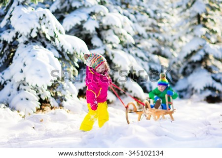 Little girl and boy enjoying sleigh ride. Child sledding. Toddler kid riding a sledge. Children play outdoors in snow. Kids sled in snowy park in winter. Outdoor fun for family Christmas vacation. - stock photo