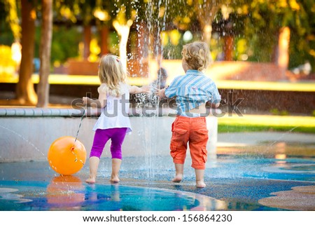 Little Girl and Boy Having Fun with the Water - stock photo