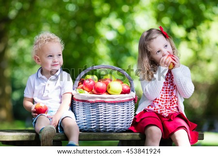 Little girl and boy in apple tree orchard.  - stock photo