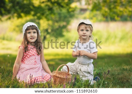 little girl and boy in the forest with punnet - stock photo