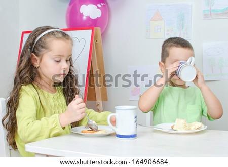 Little girl and boy is eating in kindergarten. - stock photo
