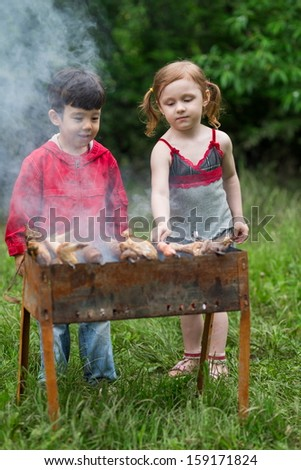 Little girl and boy making barbecue on the grill on nature