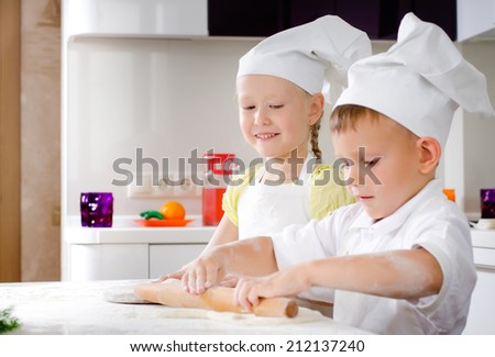 Little girl and boy making homemade pizza working together in the kitchen in their white chefs uniforms and toques rolling out the dough for the base - stock photo