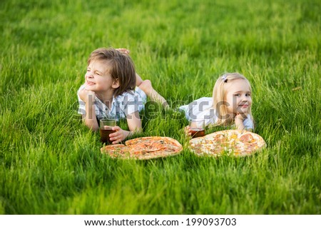 Little girl and boy outdoor summer with pizza and juice