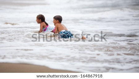 Little girl and boy playing in the surf at the ocean