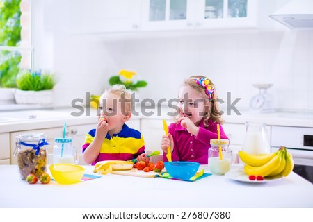 Little girl and boy preparing breakfast in kitchen. Healthy food for children. Child drinking milk and eating fruit. Happy preschooler enjoying morning meal, cereal, banana, strawberry. Kids cooking - stock photo
