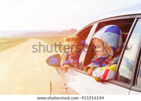 little girl and boy travel by car on the road
