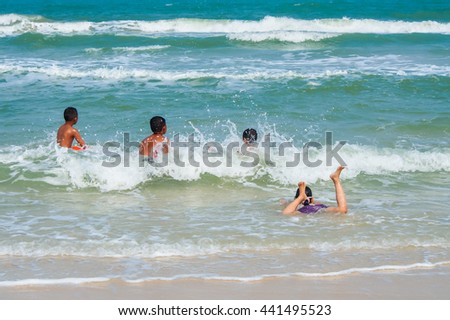 Little girl and boy waiting for wave in the sea.