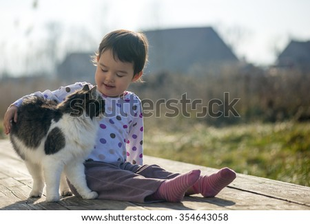 Little Girl and cat play outside - stock photo
