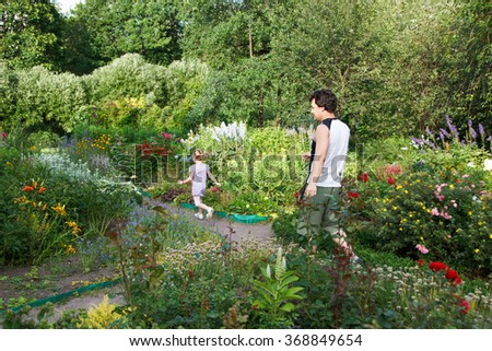 little girl and dad walking among flowers along the paths of the park - stock photo