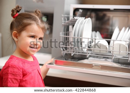 Little girl and dishwasher in the kitchen