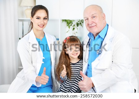 Little girl and doctors in hospital - stock photo
