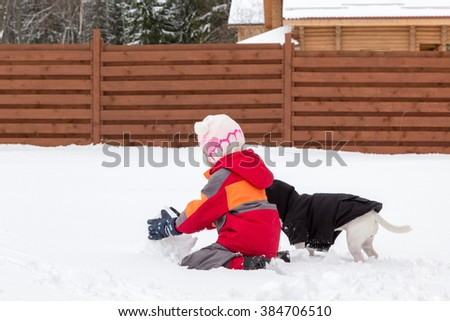 little girl and dog playing with the snow