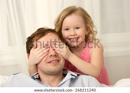 Little girl and father having fun together. She making a joke or playing hide-and-seek by closing his eyes - stock photo