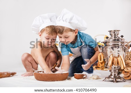 Little girl and funny boy wearing chef hats