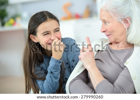 Little girl and grandma whispering secrets - stock photo