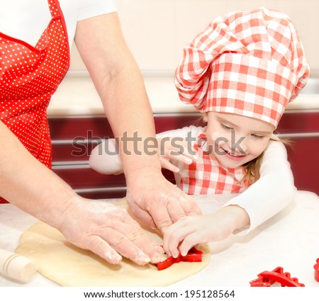 Little girl and grandmother cut dough with form  for cookies in kitchen - stock photo