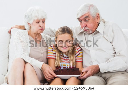 Little girl and grandparents blowing out the candles on birthday cake on couch