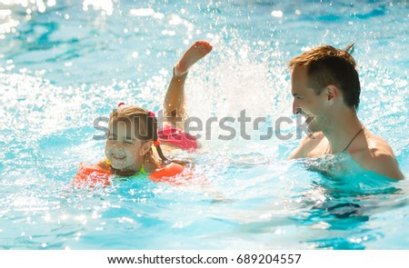 Little girl and happy father having fun in outdoors swimming pool