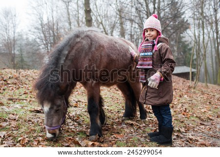 Little girl and her best friend pony at countryside outdoors - stock photo